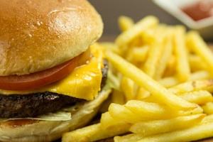 Šťavnatý hovězí hamburger s hranolkami v restauraci Na Knoflíku v Brně...